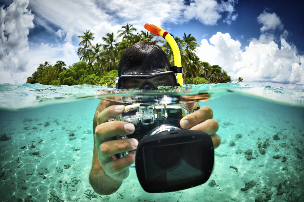 man snorkeling taking a picture with a camera